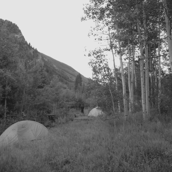 Tents near the creek under the aspen trees